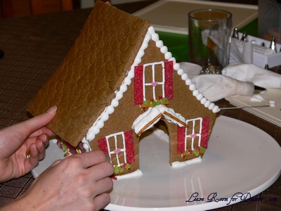 Pipe royal icing on all the edges the roof will attach to. Place roof on top and hold in place until stable.